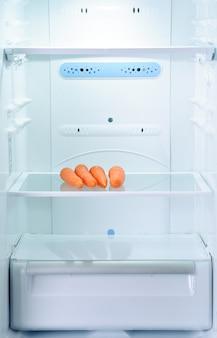 Quattro carote fresche e crude in frigorifero