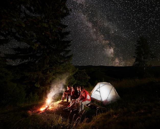 Quattro amici si siedono su un tronco vicino alla tenda godendosi la fiamma di un fuoco vicino ai bellissimi abeti sotto il cielo stellato su cui è visibile la via lattea sullo sfondo di montagne e colline.