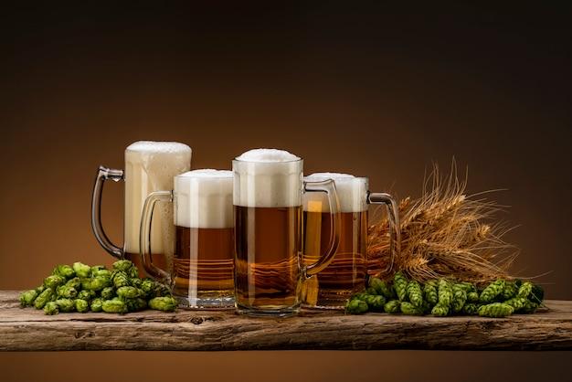 Quattro bicchieri di birra chiara per un'azienda con luppolo e grano su un tavolo di legno