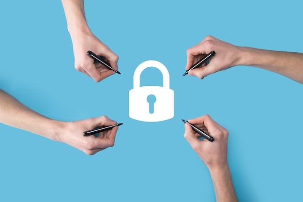 Quattro mani disegnano l'icona di un lucchetto con un pennarello. rete di sicurezza informatica.