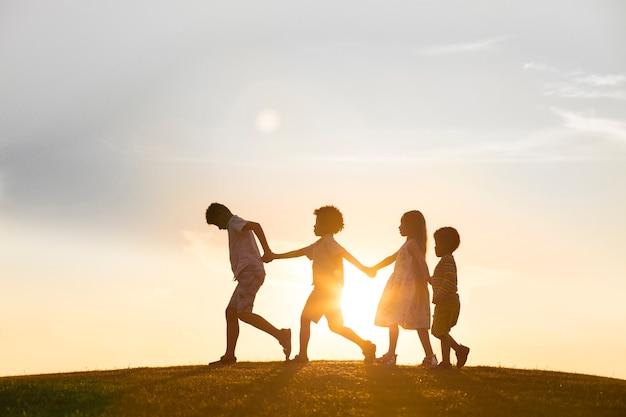 Quattro bambini felici stanno giocando al tramonto, saltano e si tengono per mano