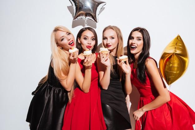 Quattro giovani donne adorabili felici in piedi e mangiano cupcakes alla festa su sfondo bianco