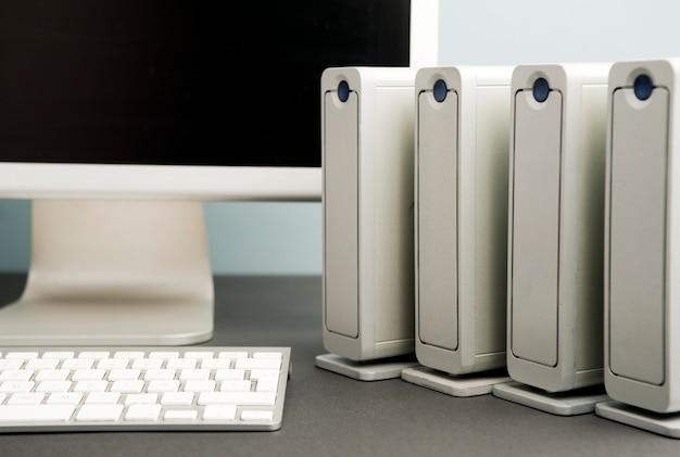 Quattro dischi rigidi con vista parziale del monitor del computer e della tastiera. sfondo grigio blu nero tavolo