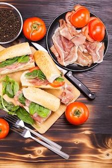 Quattro panini fatti in casa su una tavola di legno accanto agli ingredienti di cui è stato fatto