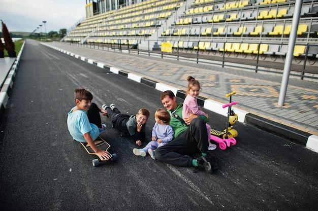 Quattro bambini con il padre in asfalto giocano e si divertono. la famiglia sportiva trascorre il tempo libero all'aperto con scooter e pattini.