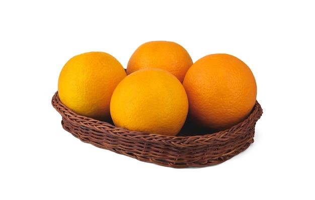 Quattro grandi arance giacciono in un cesto di vimini basso e sono isolate su uno sfondo bianco pulito con alcune ombre morbide.