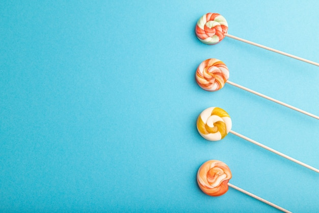 Quattro caramelle lecca-lecca su pastello blu