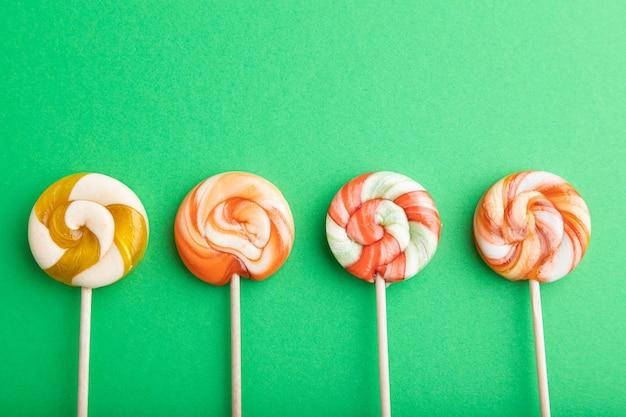 Quattro caramelle lecca-lecca su pastello verde