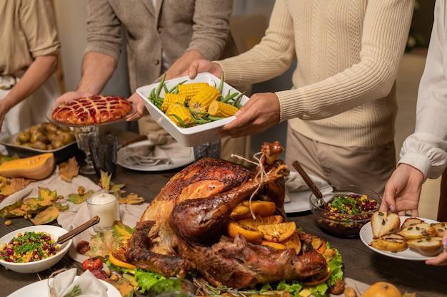 Quattro membri della famiglia mettono piatti e ciotole con dessert fatti in casa, mais al forno, insalata, torta dolce e altro cibo sul tavolo prima della celebrazione