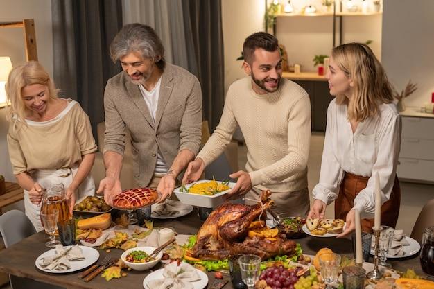 Quattro membri di una famiglia numerosa mettono piatti e ciotole con torta fatta in casa, mais al forno, insalata e altro cibo sul tavolo prima della celebrazione