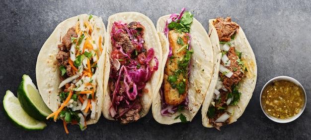 Quattro tacos di strada messicani con barbacoa di pesce e carnitas girati nella composizione panoramica