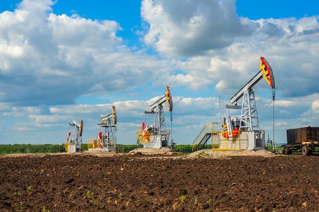 Quattro sedie a dondolo di petrolio in un campo con terreno nero