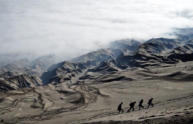 Quattro persone stanno facendo un'escursione sulle dune di sabbia sul pendio del cratere bromo, in indonesia