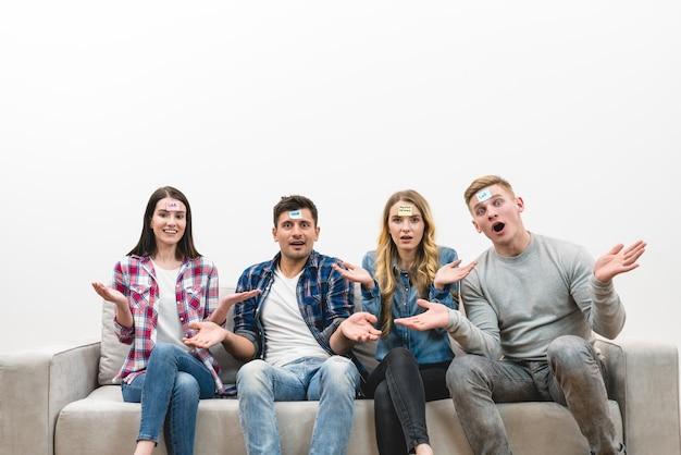 Le quattro persone sul divano giocano sullo sfondo bianco