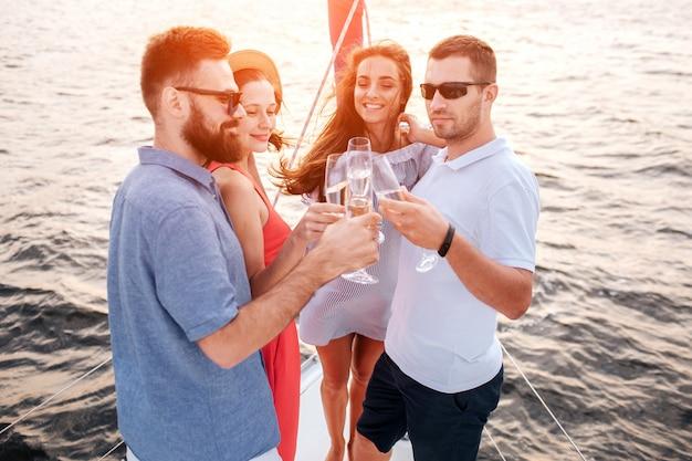 Quattro persone in piedi l'una accanto all'altra. si toccano con bicchieri di champagne. i ragazzi indossano occhiali da sole. le giovani donne sorridono e si godono il tempo.