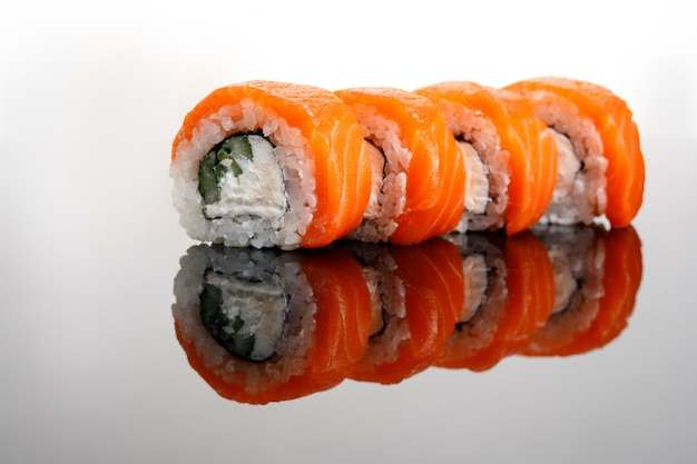 Quattro philadelphia sushi rol su un tavolo di vetro.