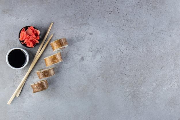 Quattro pezzi di rotoli di sushi, zenzero e soia su sfondo di pietra.