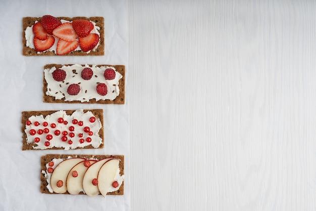 Quattro pezzi di pane croccante vegetariano con crema di formaggio e assortimento di bacche rosse. vista dall'alto