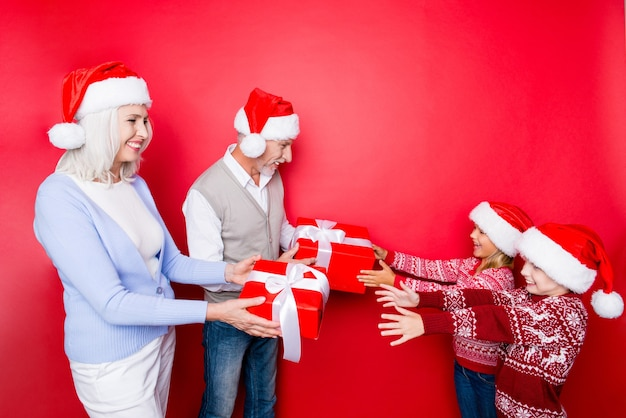 Quattro parenti: fratelli eccitati che prendono scatole di sorprese con il nastro della coppia di anziani sposati di nonno e nonna, in abiti tradizionali x mas lavorati a maglia, godono, isolato sullo spazio rosso