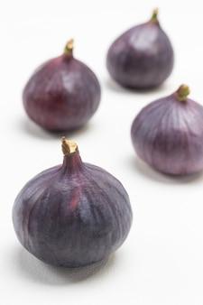 Quattro fichi viola maturi. sfondo bianco. vista dall'alto