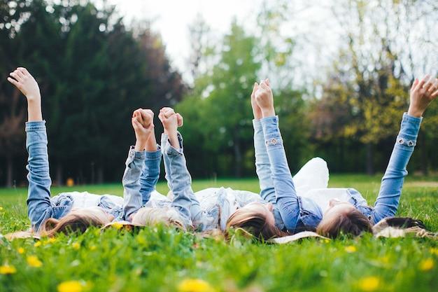 Quattro sorelle sdraiate insieme a terra