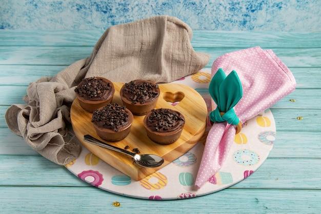 Quattro piccole torte di brigata al cioccolato su un tavolo di pasqua con tovagliolo rosa, portatovagliolo simile a orecchie di coniglio, un piatto a tema e supporto in legno