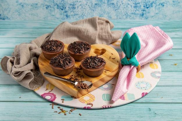 Quattro piccole torte di brigata al cioccolato su un tavolo di pasqua con tovagliolo rosa, portatovagliolo simile a orecchie di coniglio
