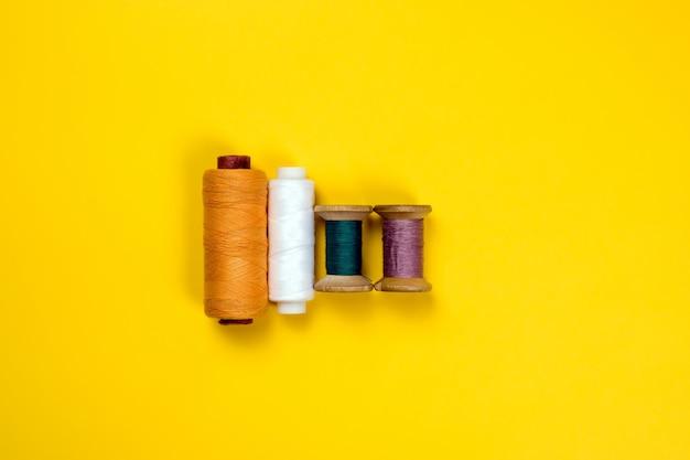 Quattro bobine di filo colorato giacciono in fila