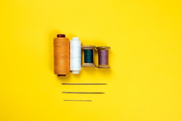 Quattro bobine di fili multicolori e tre aghi da ricamo di diverse dimensioni sotto.