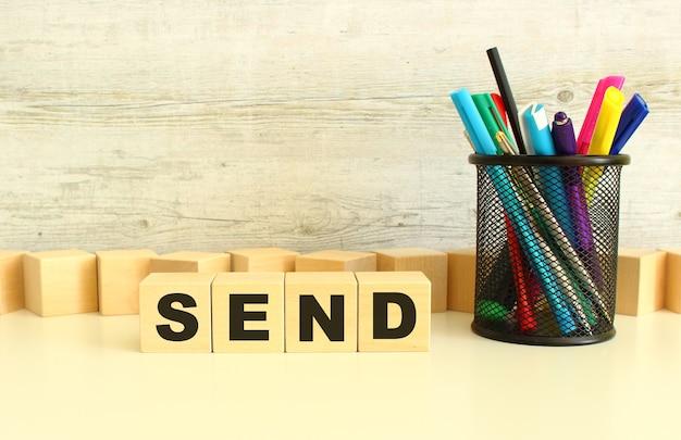 Quattro cubi di legno impilati con le lettere send su un desktop bianco su sfondo grigio.