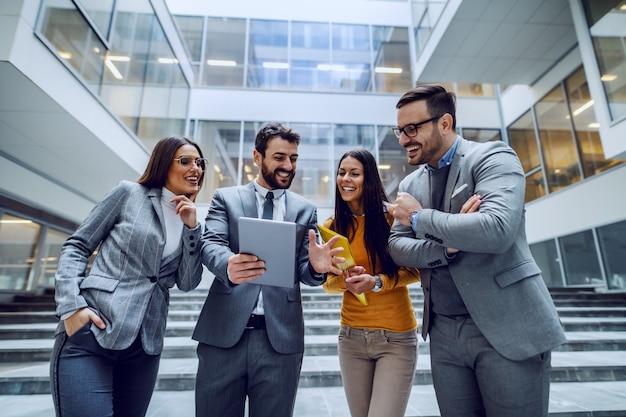Quattro imprenditori sorridenti di successo in piedi davanti all'edificio aziendale e guardando tablet quell'uomo in mezzo alla tenuta.