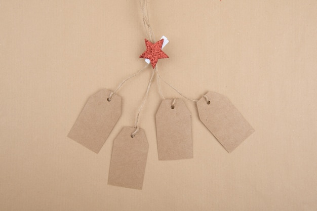 Quattro etichette di carta kraft riciclata appese a una corda decorata con una molletta da bucato con una stella rossa di natale