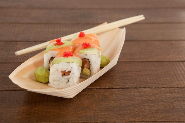 I quattro sushi di uramaki sono servito con le bacchette in zolla di legno della barca