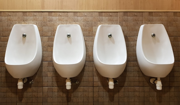 Quattro orinatoi allineati sulla parete piastrellata di un moderno bagno pubblico maschile, senza privacy.