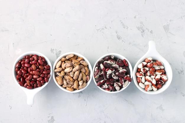 Quattro varietà di fagioli ricchi di proteine situate su uno sfondo di cemento grigio, vista dall'alto