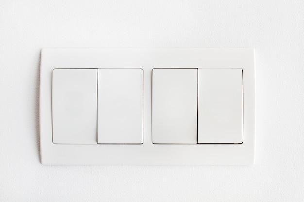 Quattro interruttori della luce bianca su un muro bianco ibn una vista ravvicinata