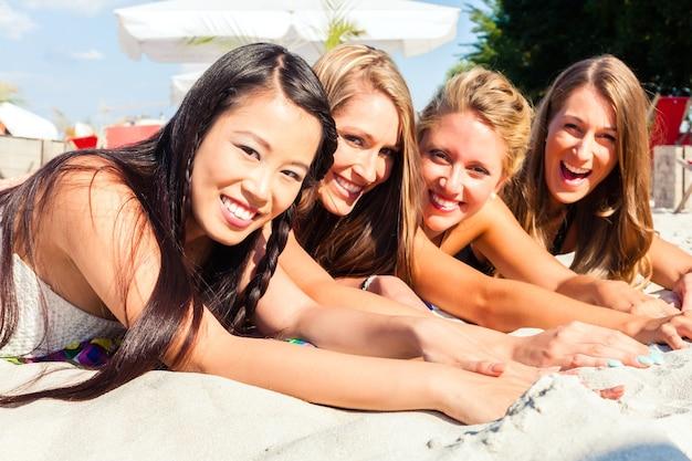 Quattro donna sdraiata sulla spiaggia di sabbia, abbronzandosi al sole