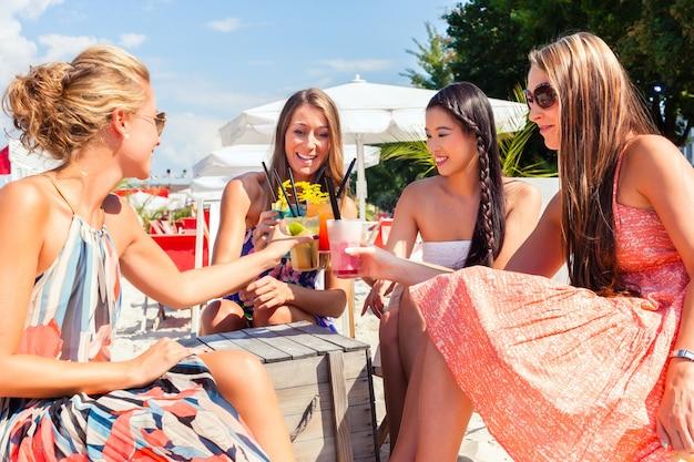 Quattro donna seduta in un bar sulla spiaggia, bevendo cocktail fantasiosi e abbronzandosi al sole