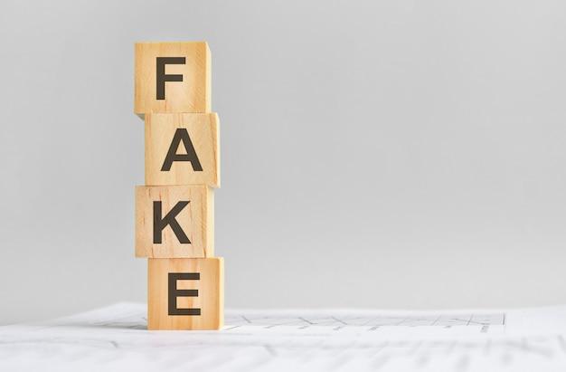 Quattro cubi di legno con la parola falso sullo sfondo di rendiconti finanziari bianchi, forte concetto di business. sfondo grigio