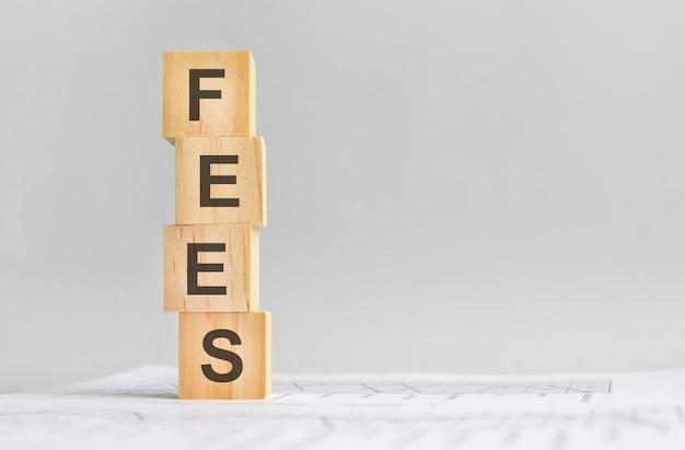 Quattro cubi di legno con la parola commissioni sullo sfondo di rendiconti finanziari bianchi, forte concetto di business. sfondo grigio