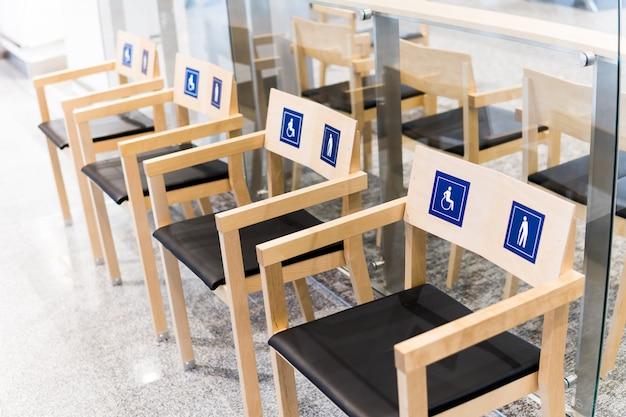 Quattro sedie in legno all'aeroporto con cartelli per disabili e anziani. assegnazione di posti pubblici ai disabili
