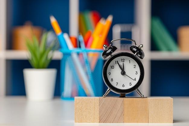Quattro cubi di legno e sveglia sulla scrivania