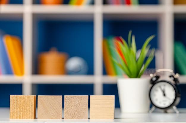 Quattro cubi di legno con copia spazio e sveglia sulla scrivania