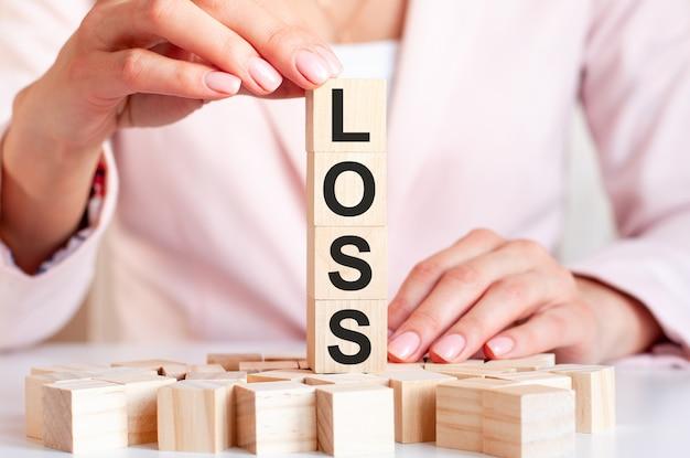 Quattro cubi di legno con la parola perdita, contro le mani femminili in abiti rosa. affari, finanza e concetto economico.