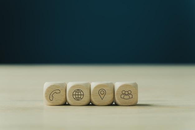 Quattro dadi di legno con icone di contatto e informazioni posizionati in fila. su sfondo blu con copia spazio.