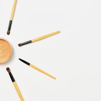 Quattro pennelli trucco manico in legno con base in polvere, cipria isolato su bianco. polvere sciolta di trucco mezzo viso in un barattolo aperto con spazzole per il viso su sfondo bianco. concetto di bellezza e cosmetici.