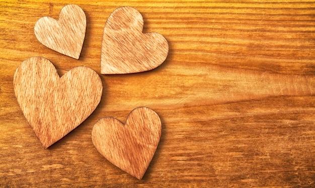 Quattro cuori di legno sul tavolo di legno