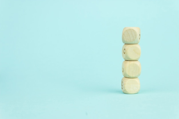 Quattro cubi giocattolo in legno disposti in verticale su sfondo blu, crescita aziendale e concetto di gestione. blocchi cubici di legno vuoti.