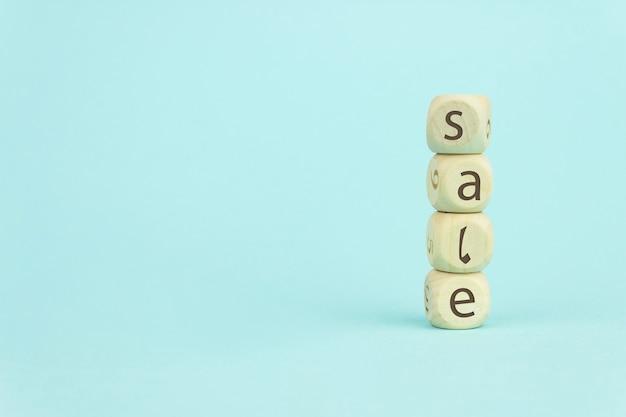 Quattro cubi giocattolo in legno disposti in verticale su sfondo blu con testo vendita, crescita aziendale e concetto di vendita estiva.