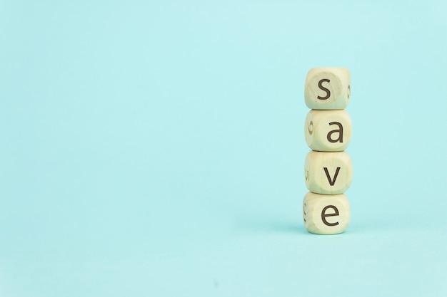 Quattro cubi giocattolo in legno disposti in verticale su sfondo blu con testo salva, crescita aziendale e concetto di salvataggio.